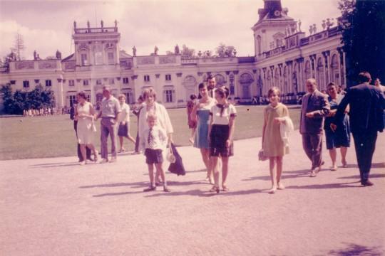 Kolorowe zdjęcie. Grupa ludzi idzie drogą na dziedzińcu. Za nimi pałac.
