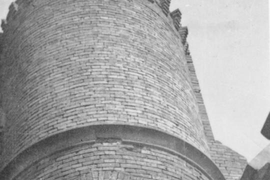 Zbliżenie na fragment murowanej wieży z perspektywy żabiej. Mężczyzna siedzi w wąskim podłużnym oknie. Wystawia zgiętą nogę na parapet.