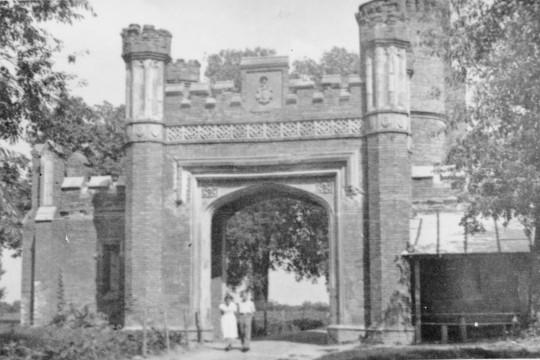 Kobieta i mężczyzna przechodzą przez neogotycką bramę.