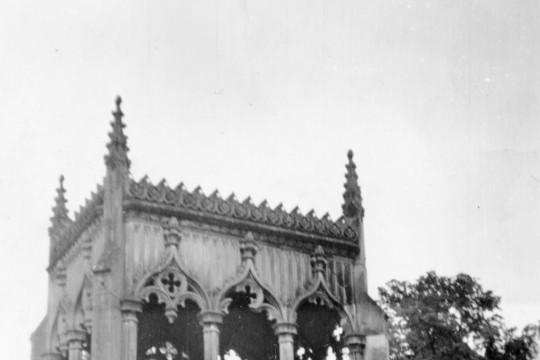 Trzy kobiety siedzą na murku pod mauzoleum Potockich.
