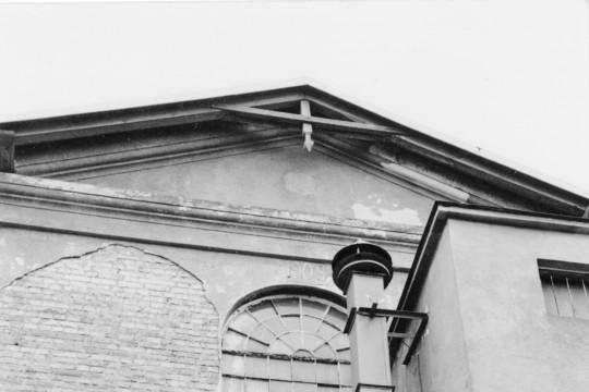 Zbliżenie na fragment budynku. Pod oknem znajduję się płaskorzeźba z herbem Pilawa.