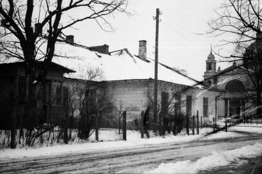 Zima. Ośnieżona droga. Obok niej murowany dom z drewnianym gankiem. W oddali widać Kościół Świętej Anny.