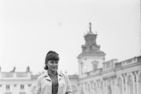 Kobieta w jasnej garsonce. W jednej ręce trzyma torebkę, drugą unosi na wysokość brzucha. W tle niewyraźny pałac.
