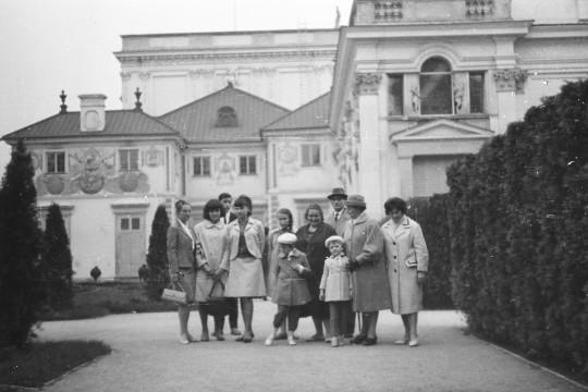 Grupa osób, dorosłych i dzieci, stoi razem w zwartej grupie. Parzą przed siebie. Za nimi północna część korpusu pałacowego.