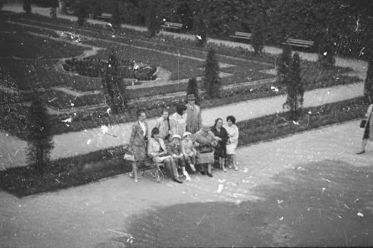 Fotografia lekko zniszczona, pełna małych białych plamek. Widok z Tarasu Górnego na grupę osób. Niektórzy siedzą na ławce, cztery osoby stoją za nią.