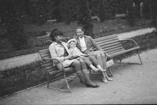 Dwie kobiety odpoczywają na ławce w wilanowskim parku. Między nimi dziecko oparte o oparcie, nie dosięga nogami do ziemi.