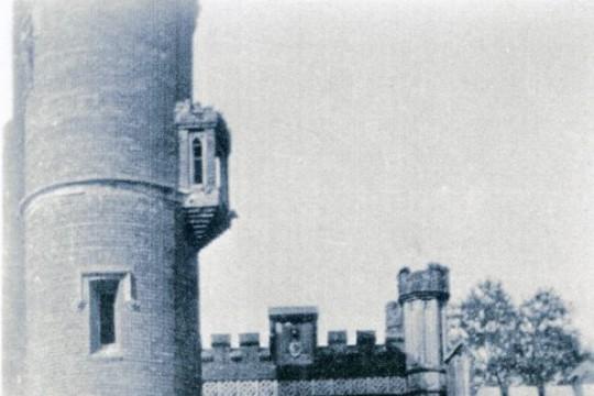 Pięć kobiet w roboczych sukienkach i chustach na głowach stoi na tle neogotyckiej bramy. Z lewej strony bramy wysoka wieża.