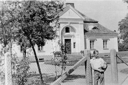 Mężczyzna stoi przy ogrodzeniu z siatki. Za nim murowany dworek.