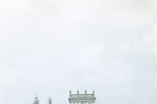 Dziewczynka w luźnej białej koszulce stoi prosto na dziedzińcu. W tle korpus główny pałacu.