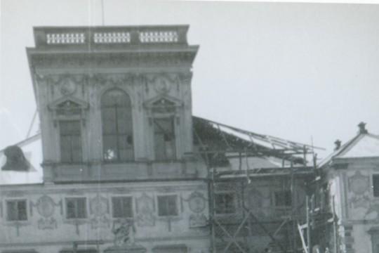 Dziecko stoi z kwiatkiem w ręku. W tle fragment pałacu. Pałac jest w remoncie, przy fasadzie postawiono rusztowania.