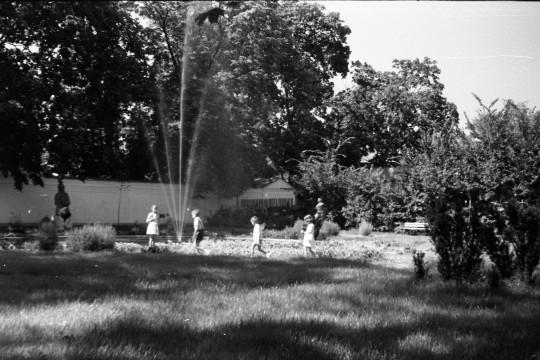 Ogród. Czworo małych dzieci idzie jedno za drugim obok fontanny. Wysoki strumień tryska do góry.