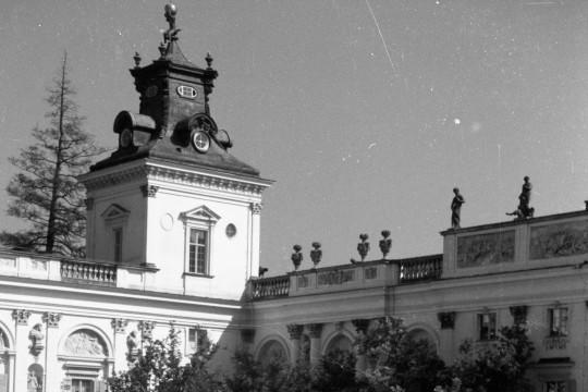 Na dziedzińcu pałacu stoi troje dzieci. Stoją od najwyższego do najniższego, obejmują się ramionami. Za nimi fragment pałacu.