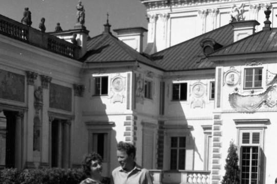Teresa Rybka i Jerzy Rybka na spacerze w wilanowskich ogrodach. Stoją pod rękę, patrzą na siebie, w tle korpus główny pałacu (widok od strony południowej).