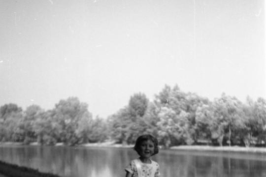 Droga przy Jeziorze Wilanowskim. Dziewczynka skacze na skakance. Zastygła w powietrzu. Ręce opuszczone, skakanka pod stopami dziewczynki.