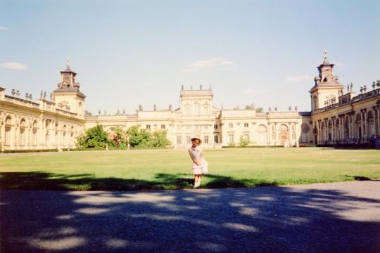 Kolorowe zdjęcie. Na dziedzińcu mała dziewczynka pozuje z biodrem wypchniętym w lewo i rękami złożonymi z przodu.  W tle pałac wilanowski.