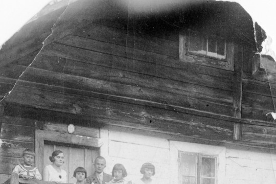 Grupa osób stoi na drewnianych schodach prowadzących do wejścia do Gajówki w Morysinie.