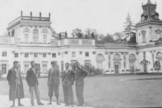 Pięciu mężczyzn w garniturach pozuje na dziedzińcu. W  tle pałac. Stoją nonszalancko, jeden opiera rękę na biodrze, drugi trzyma ręce w kieszeniach spodni, jeden trzyma ręce za plecami.