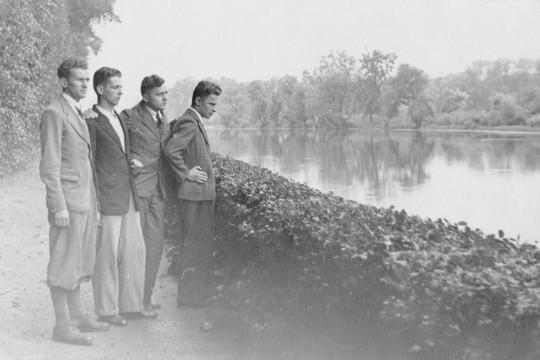 Ujęcie bokiem. Czterech młodych mężczyzn w garniturach stoi przy niskim żywopłocie oddzielającym ścieżkę od Jeziorka Wilanowskiego.  Patrzą przed siebie, trzymają sobie nawzajem ręce na ramionach.