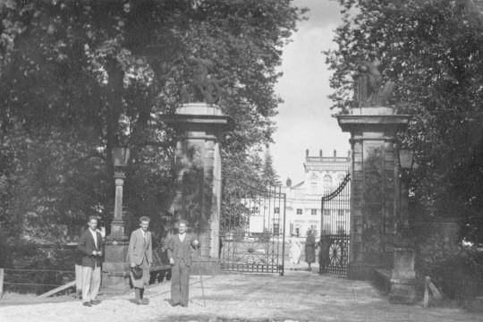 Trzech młodych mężczyzn w garniturach pozuje na tle bramy głównej. Brama jest uchylona, po drugiej stronie bramy, na dziedzińcu,  stoją trzy kobiety. Po bokach bramy rozłożyste korony drzew, w tle pałac.